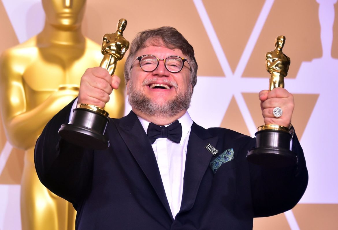 Director Guillermo del Toro poses in the press room with the Oscars for best picture and best director during the 90th Annual Academy
